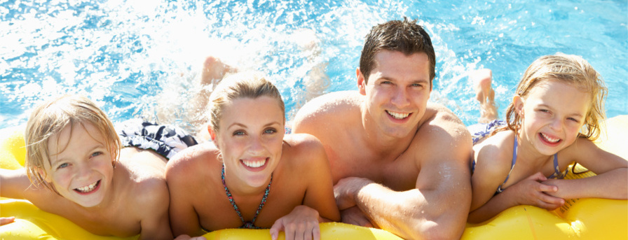 Young family having fun together in heated pool